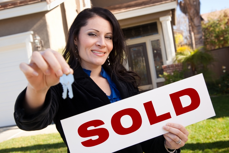 932935-hispanic-woman-holding-keys-and-sold-sign-in-front-of-house