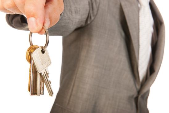 Säljare står med nyckeln till ditt nya hus